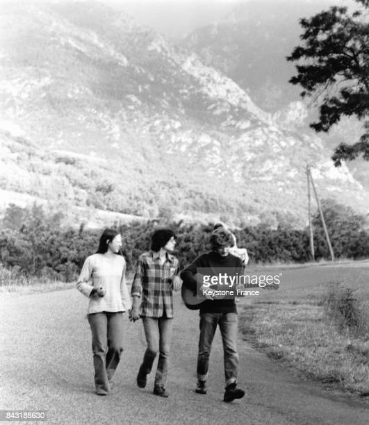Un groupe d'adolescents avec une guitare marche sur une route dans la montagne circa 1970 en France