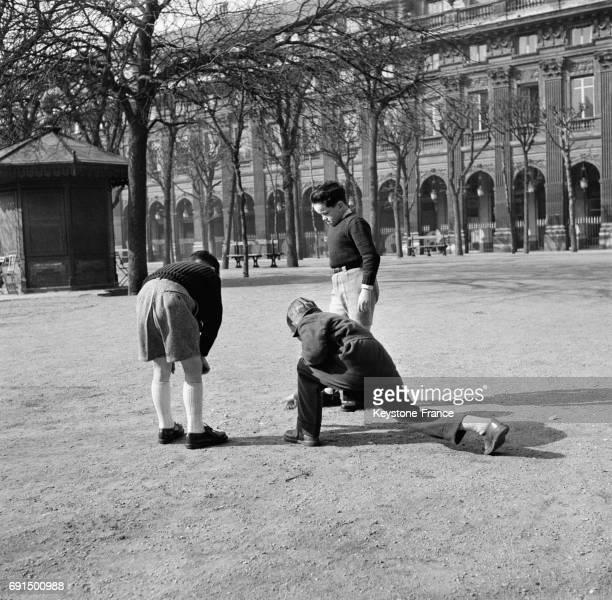 Un groupe de jeunes hommes jouent à la pétanque dans le Jardin du Palais Royal sous le soleil à Paris France le 2 mars 1953