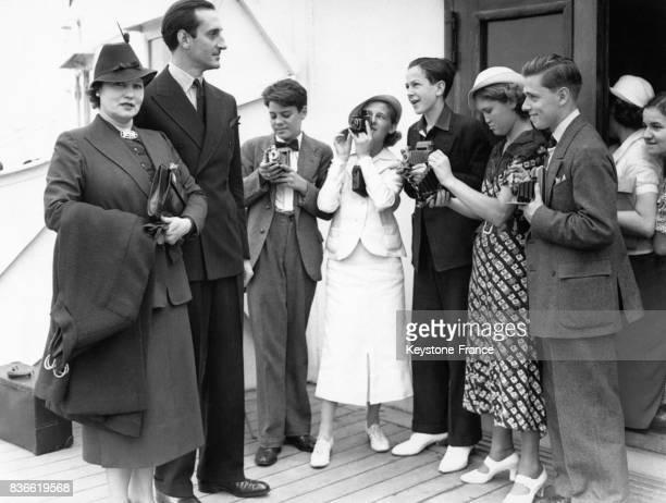 Un groupe de jeunes photographes amateurs chassant les stars de cinéma prennent en photo l'acteur britannique Basil Rathbone et sa femme à New York...