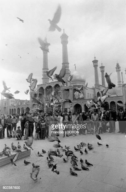 Un groupe de personnes regardant des pigeons devant le mausolée de Hazrat Masoumeh dans le ville sainte de Qom le 29 mars 1979 Iran