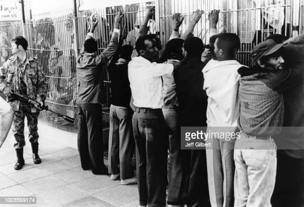 Un groupe d'émeutiers noirs les mains en l'air le long d'une grille sont surveillés par un militaire blanc armé d'une mitraillette en juin 1976 à...