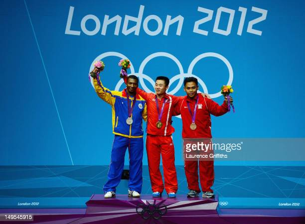 Un Guk Kim of DPR Korea celebrates with the gold medal Oscar Albeiro Figueroa Mosquera of Colombia with the silver medal and Irawan Eko Yuli of...