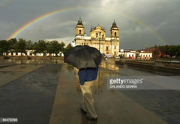 Un hombre camina el 11 de junio de 2003 por la Plaza de la Constitución en la ciudad de Guatemala mientras observa el arcoiris que se forma sobre la...