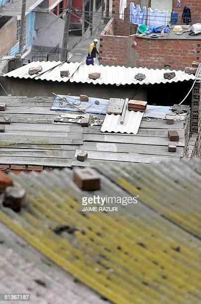 Un hombre cruza una calle de un barrio marginal de la zona norte de Lima el 23 de setiembre de 2004 La mayor parte de las edificaciones de estos...
