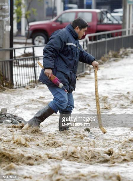 Un hombre intenta cruzar una calle barrida por el agua de la lluvia en la comuna de la Reina en Santiago el 28 de agosto de 2005 El mal tiempo que...