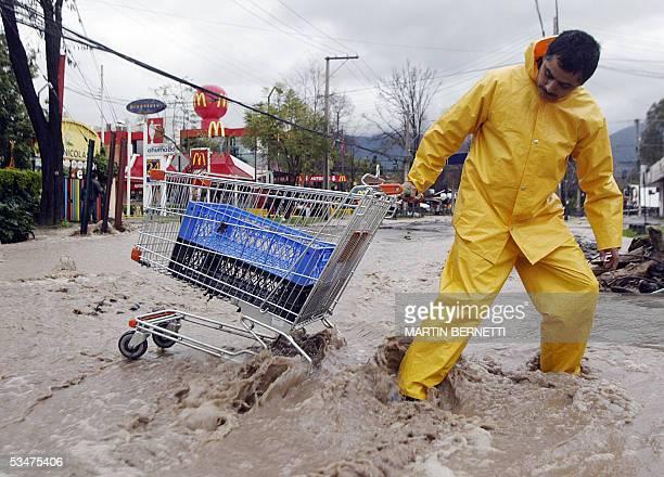 Un hombre intenta cruzar una calle inundada con un carrito de compras en la Comuna de la Reina en Santiago el 28 de agosto de 2005 El mal tiempo que...
