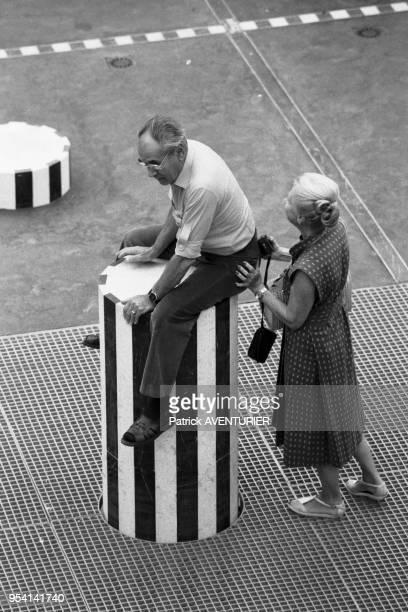 Un homme aidé par sa femme grimpe sur les colonnes de Buren à Paris le 9 aout 1986 France