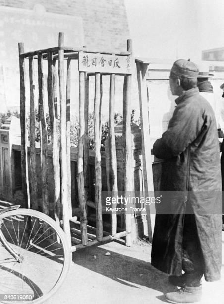 Un homme chinois observe une cage en bois dans laquelle sont enfermés les marchands chinois ayant vendu des marchandises aux Japonais lors du conflit...