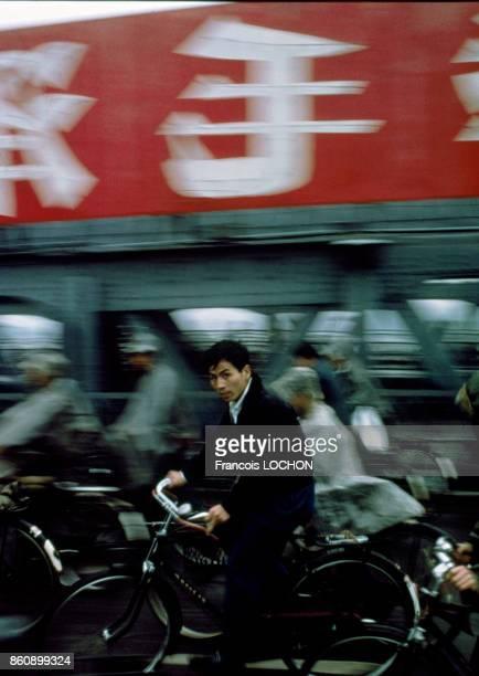 Un homme circule sur son vélo au milieu d'autres cyclistes en octobre 1980 à Pékin Chine
