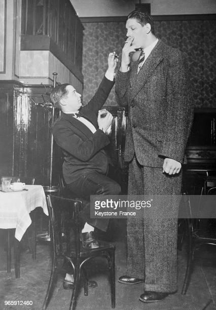 Un homme debout sur une chaise allume la cigarette du géant finlandais Vaine Myllyrinne mesurant 250 mètres à Vienne Autriche le 23 février 1935