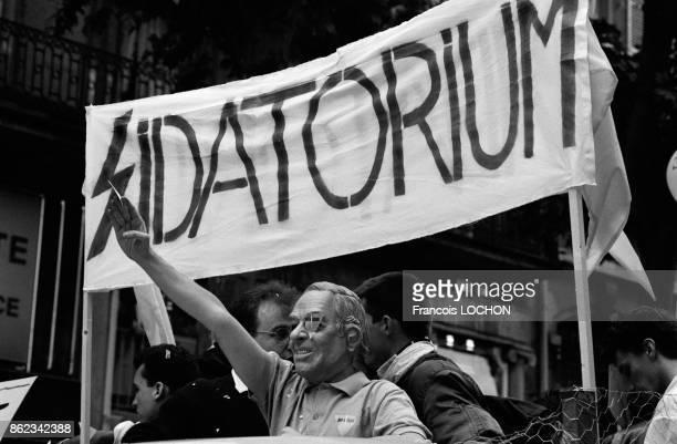 Un homme déguisé en JeanMarie Le Pen faisant le salut nazi devant une banderole 'Sidatorium' lors de la Gay Pride dans les rues de Paris le 20 juin...
