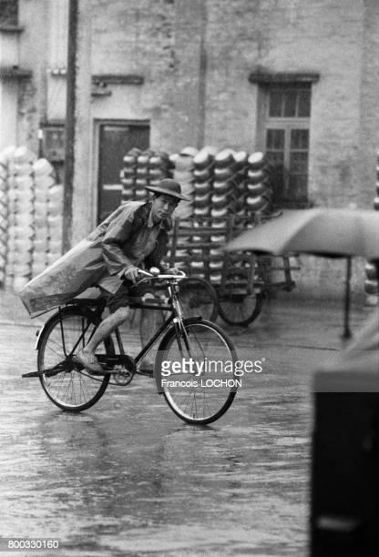 Un homme en bicyclette sous la pluie dans une rue de Pékin en février 1979 en Chine
