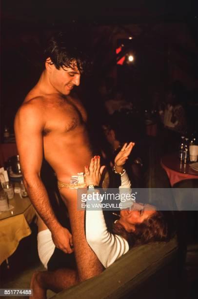 Un homme en maillot de bain chevauche une spectatrice dans le public d'un club érotique pour femmes en mars 1992 à Caracas Venezuela