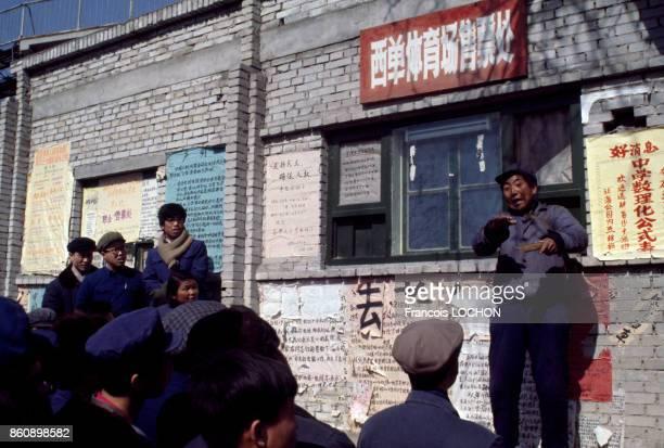 Un homme en tenue d'ouvrier parle de politique aux passants groupés devant un mur couvert de dazibaos en janvier 1978 à Pékin Chine