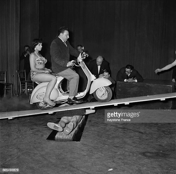 Un homme et sa passagère en deux roues roule sur une planche sous laquelle est allongé un fakir sur une planche à clous lors d'un spectacle à...