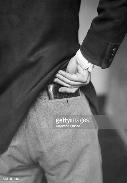 Un homme glisse son portefeuille dans la poche arrière de son pantalon