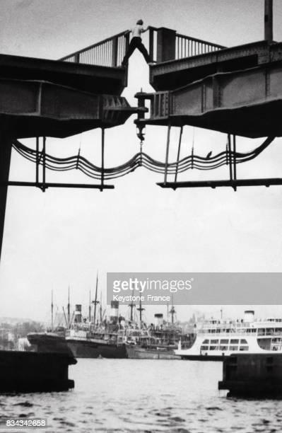 Un homme grimpe d'un côté à l'autre du pont d'Atatürk sur la Corne d'Or car il n'a pas pu attendre que les deux bouts de ce pont mobile se joignent à...
