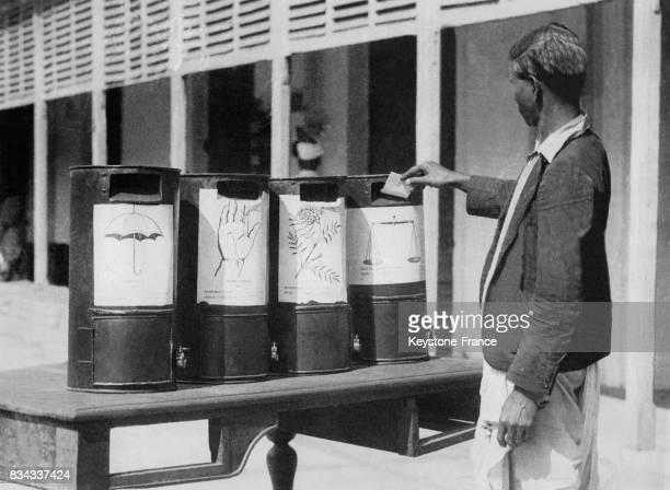 Un homme met son bulletin dans l'urne les boites sont ornées de symboles permettant aux illettrés de voter à Calcutta Inde