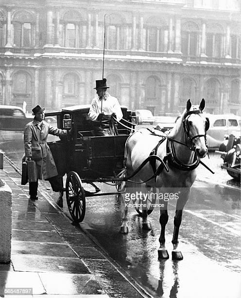 Un homme portant des malettes à côté d'un attelage faisant la liaison entre Buckingham Palace et le siège du gouvernement à Whitehall, à Londres,...
