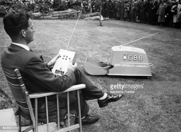 Un homme utilise la première tondeuse à gazon téléguidée à Londres RoyaumeUni le 26 mai 1959