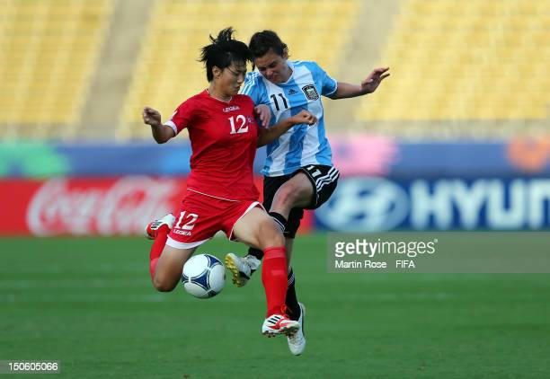 Un Hyang Kim of Korea DPR and Maria Bonsegundo of Argentina battle for the ball during the FIFA U20 Women's World Cup 2012 group C match between...