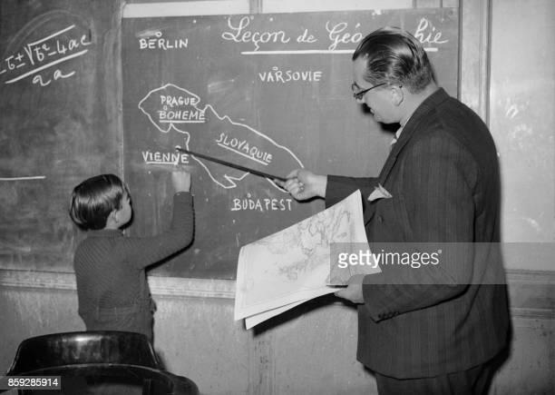 Un instituteur d'une école primaire parisienne explique le 10 octobre 1938 à un élève les événements survenus en Europe Centrale après la signature...