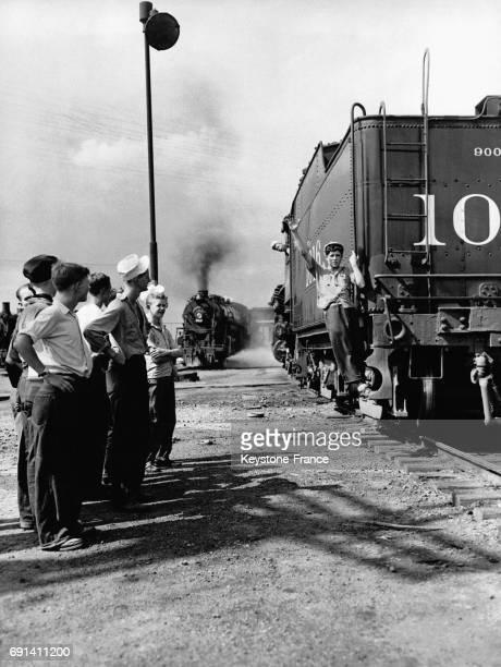 Un jeune apprenti cheminot à bord d'une locomotive à vapeur donnant le signal pour changer d'aiguillage devant ses camarades le 25 juin 1944 à...