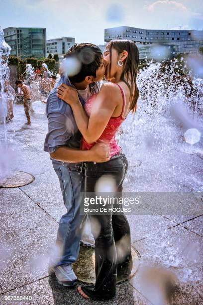 Un jeune couple s'embrassant sous les jets d'eau du Parc André Citroën pendant la canicule de Juillet 2003 à Paris France