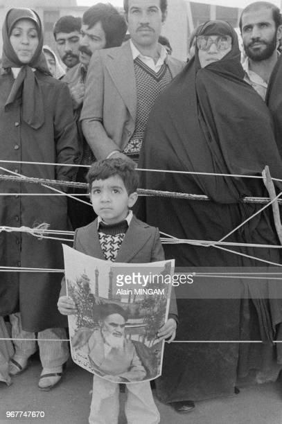 Un jeune garçon iranien tenant un portrait de l'ayatollah Khomeini lors de la libération de trois otages le 18 novembre 1979 Téhéran Iran