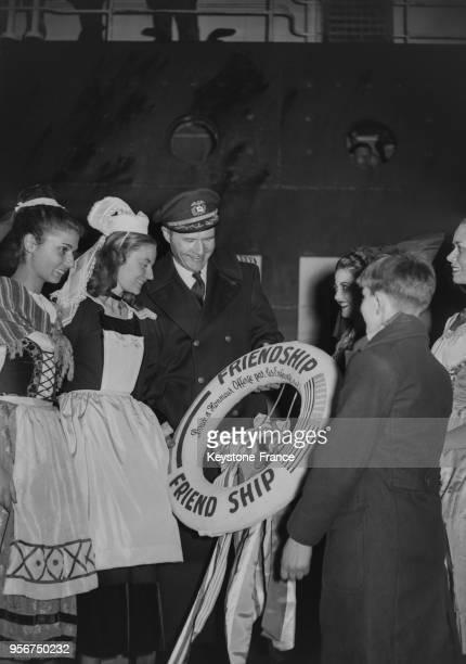 Un jeune Havrais entouré de jeunes filles en costume régional offre une bouée symbolique au commandant du navire 'American Leader' qui a transporté...