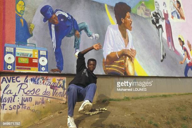 Un jeune homme entrain de danser le smurf devant une fresque murale à la Cité des 3000, en octobre 1984 à Aulnay-sous-Bois, France.