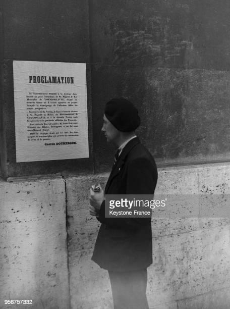 Un jeune homme lit la proclamation du gouvernement français rédigée après l'assassinat du Roi Alexandre 1er de Yougoslavie a Marseille et affichée...