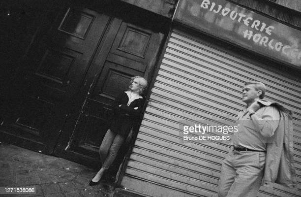 Un jeune homme passe devant une bijouterie fermée, une jeune femme prostituée se tient debout devant une porte d'entrée attendant un client, rue...