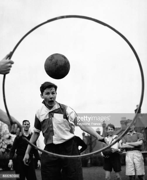 Un jeune joueur de football suivant les conseils du footballeur professionnel George Smith lors un entraînement avec les jeunes élèves du Saint...