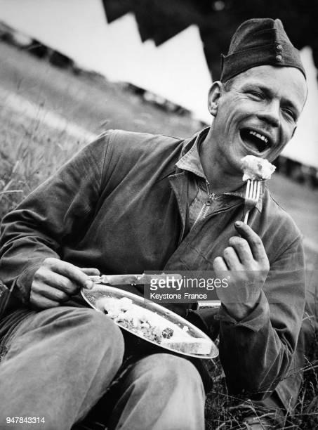 Un jeune soldat tout sourire mange pendant sa pause déjeuner lors des manoeuvres dans la région de l'EstAnglie au RoyaumeUni circa 1930