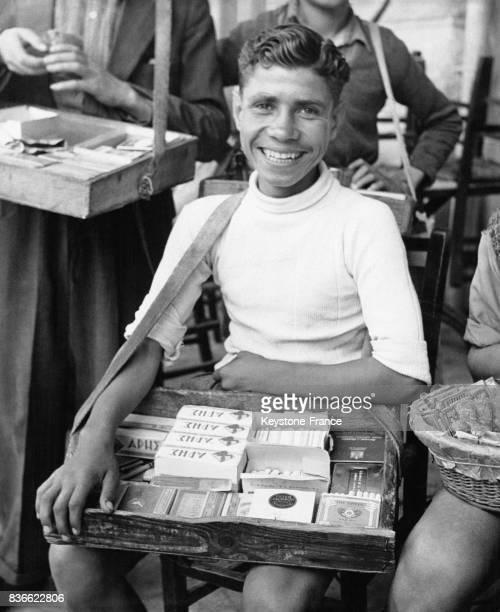 Un jeune vendeur de rues vend des cigarettes américaines à des prix exorbitants à Athènes en Grèce