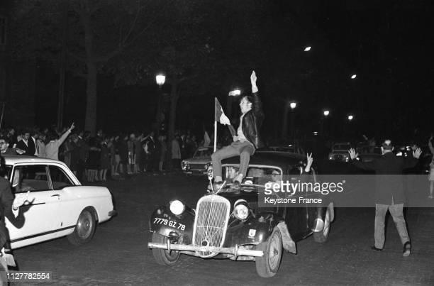 Un manifestant assis sur une voiture brandit un drapeau tricolore en soutien au général de Gaulle à Paris France le 31 mai 1968