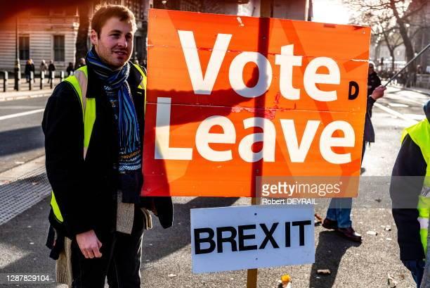 """Un manifestant pro-Brexit avec une pancarte """"VOTE LEAVE"""" et """"BREXIT"""" devant le 10 Downing Street lors des élections législatives le 13 décembre 2019..."""