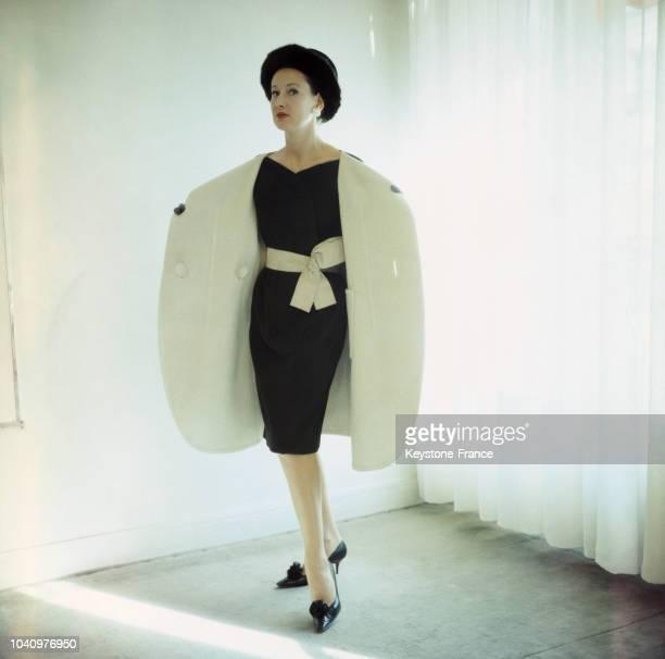 Un mannequin présente un manteau réversible Michel Goma sur une robe en lainage noir de Gérondeau avec un chapeau de Jean Barthes lors du défilé pour...
