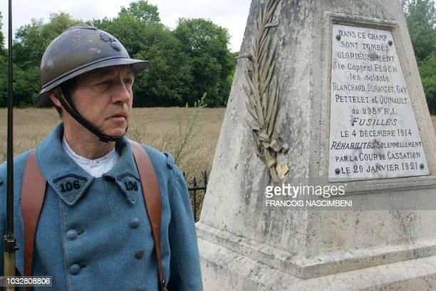 """Un membre de l'association """"Soissonnais 14-18"""" habillé en poilu, se tient, le 29 juin 2007 à Vingré, devant un monument dédié à six soldats fusillés..."""