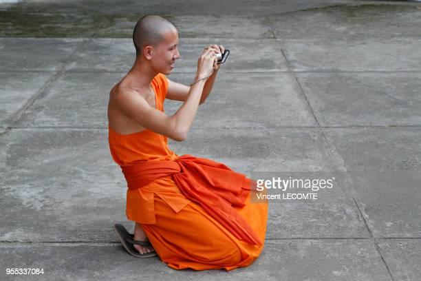 Un moine bouddhiste asiatique en tenue traditionnelle prend une photographie dans son sanctuaire bouddhiste à Luang Prabang Laos en novembre 2012