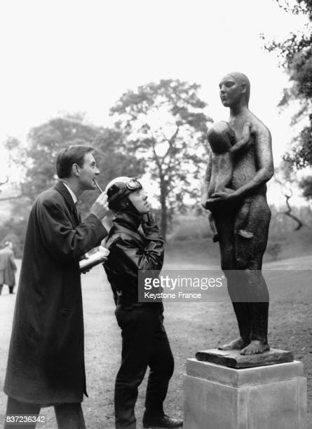 Un motard et un homme muni d'un blocnote observent la statue de bronze 'Mother and Child' de Jacob Epstein exposée dans Battersea Park le 18 mai 1960...