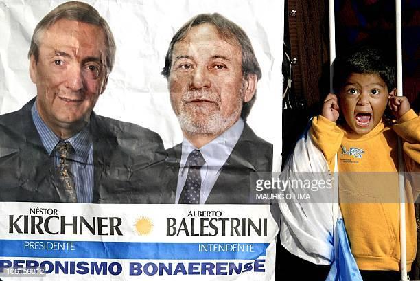 Un niño reacciona junto a un cartel del candidato peronista a la presidencia de Argentina por el Frente para la Victoria Néstor Kirchner el 24 de...