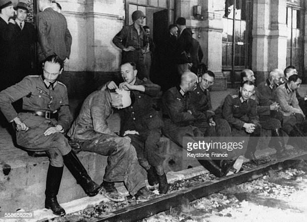 Un officier allemand bande la blessure d'un autre officier alors que l'état major du Général Dietrich von Choltitz est assis sur le quai à la gare...