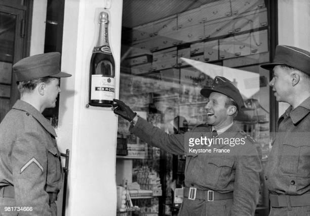 Un officier allemand de la Bundeswehr venant participer à des manoeuvres militaires en France montre à ses soldats la publicité d'une marque de...