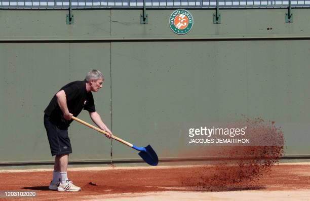 Un ouvrier prépare la terre battue d'un court de tennis le 09 avril 2010 au stade de Roland-Garros à Paris. Le tournoi de tennis de Roland Garros se...