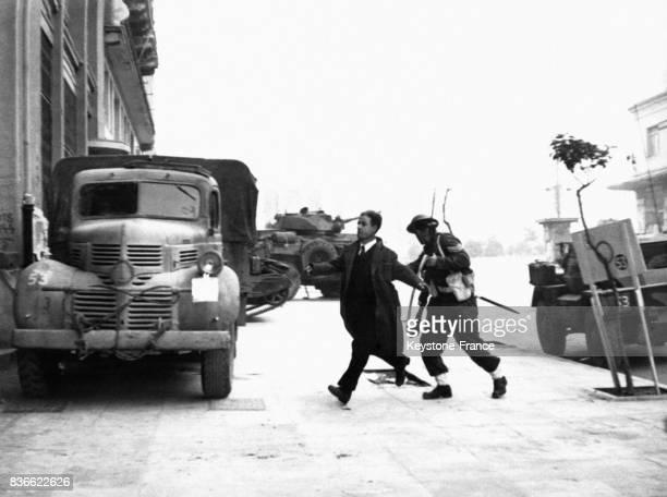 Un partisan de l'ELAS est entraîné par un parachutiste loin du bâtiment de l'ELAM d'où il tirait en 1945 à Athènes Grèce