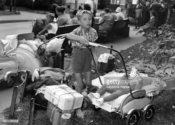 Un petit garcon ayant fui le controle sovietique surveille sa petite soeur dans un centre de refugies a BerlinOuest Allemagne
