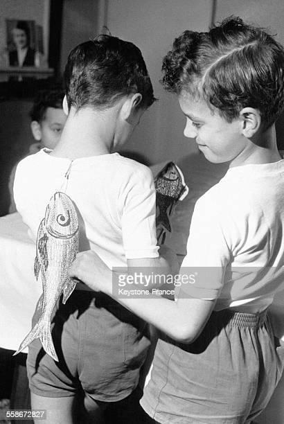 Un petit garçon accroche un poisson d'avril dans le dos de son frère pendant que ce dernier en prépare un le 29 mars 1963 en France