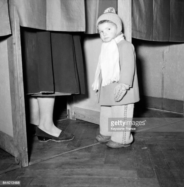 Un petit garçon attend devant l'isoloir tandis que sa maman vote à Paris France le 2 janvier 1956